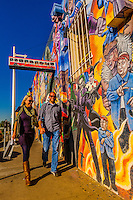 Couple walking along Central Avenue (historic Route 66) in Nob Hill, a mural of comic book super heroes in background, Albuquerque, New Mexico USA