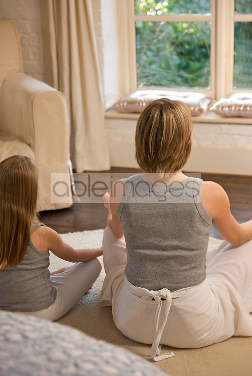 Back view of mother and daughter practicing yoga