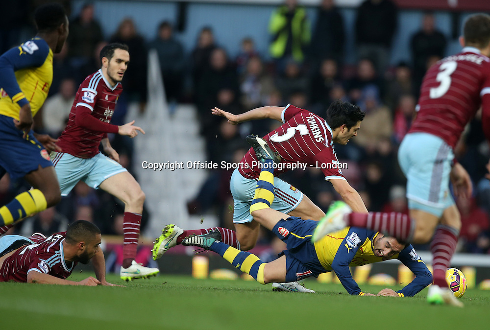 28 December 2014 Premier League Football - West Ham United v Arsenal; Santi Cazorla goes down after a tackle by Winston Reid of West Ham (bottom left) which led to a penalty for Arsenal.<br /> <br /> Photo: Mark Leech