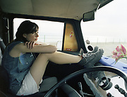 Young woman sitting in van with feet on dashboard.