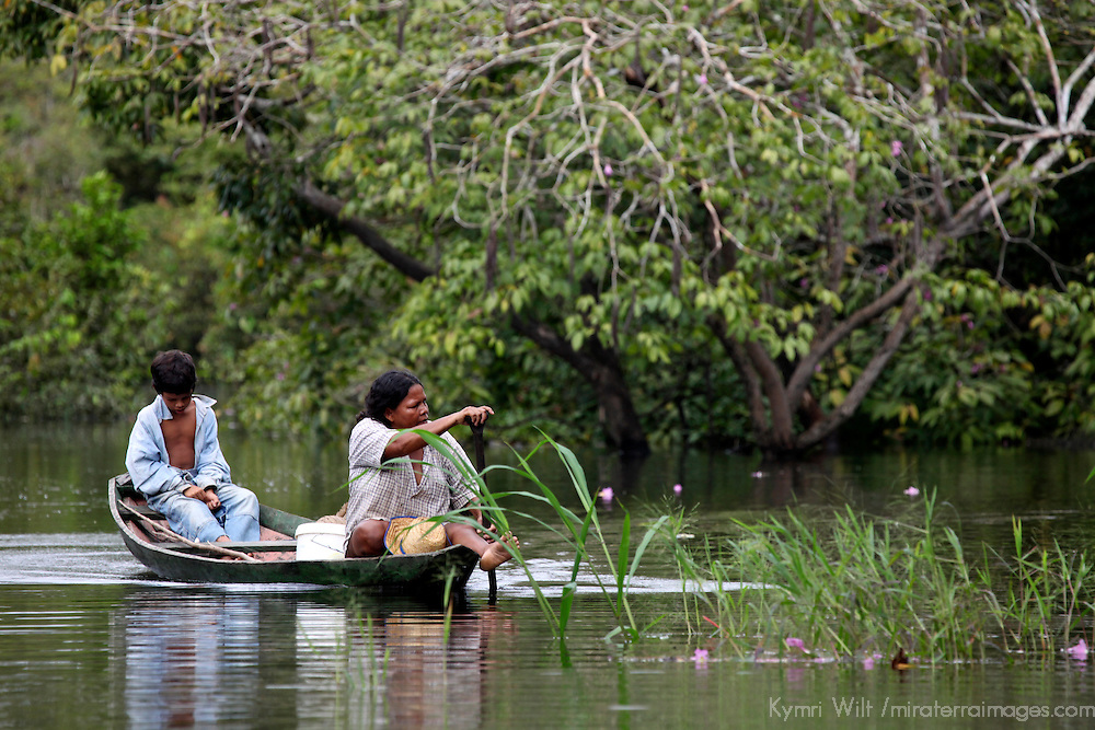 South America, Brazil, Amazon.  A woman rows as the man dozes on the Amazon.