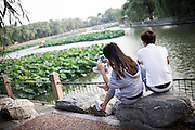 A Chinese girl plays with her smartphone close to her boyfriend on the Bei Hai lake in Beijing, China, July 20, 2014.<br /> <br /> Smartphones are an essential tool of Chinese ordinary life. Everywhere in China, people use them to take pictures to share online, to talk and chat, to play videogames, to get access to the mainstream information, to get connected one each other. In the country where the main global social media are forbidden - Facebook, Twitter and Youtube are not available  -, local social networks such as WeChat have a wide spread all over the citizens. The effect is an ordinary and apparently compulsive way to get easy access to digital technology and modern way of communication. <br /> A life through the display. Yes, We Chat.<br /> <br /> © Giorgio Perottino
