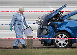© Licensed to London News Pictures. 26/09/2016. London, UK. A forensics officer inspects a damaged car near where a man was fatally stabbed. Police were called to to a disturbance in Braintree Road on Sunday evening 25th September 2016 where officers found a man in his thirties suffering from stab wounds. He died at the scene a short while later. A murder investigation has been launched. Photo credit: Peter Macdiarmid/LNP