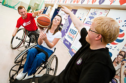 Cadbury 2012 Paralympic demonstration Sheffield..Kraft Lab scientist Kayleigh Jones tries her hand at wheelchair basketball alongside (left) coach Andy Atkinson and player Mike Porter who were on site with the  RGK Rhinos Sporting club wheelchair basketball team to give Sheffield colleagues an insight into Wheelchair basketball, Paralympic sports and promote awareness around the different sporting disciplines.   .  ....3 September 2012.Image © Paul David Drabble