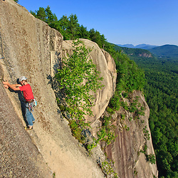 "A man climbs ""Top of the Prow"" on Cathedral Ledge.  Echo Lake State Park in North Conway, New Hampshire.  White Mountains."
