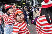 Young Chinese students dress in Wheres Wally costumes during a game in Statue Square in Central District, Hong Kong.