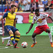Aaron Ramsey, (left), Arsenal, passes past Ambroise Oyongo. New York Red Bulls, during the New York Red Bulls Vs Arsenal FC,  friendly football match for the New York Cup at Red Bull Arena, Harrison, New Jersey. USA. 26h July 2014. Photo Tim Clayton