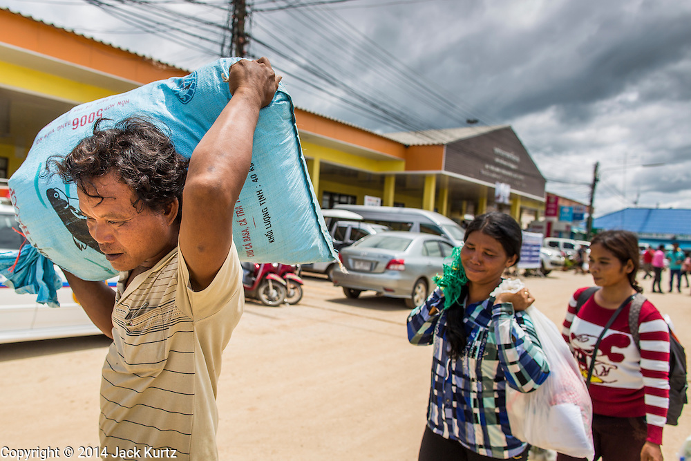 09 JULY 2014 - ARANYAPRATHET, SA KAEO, THAILAND: A family of Cambodian migrant workers walk away from the Thai Immigration One Stop Service Center in Aranyaprathet on the Thai-Cambodian border after they registered for temporary ID documents. More than 200,000 Cambodian migrant workers, most undocumented, fled Thailand in early June fearing a crackdown by Thai authorities after a coup unseated the elected government. Employers have been unable to fill the vacancies created by the Cambodian exodus and the Thai government has allowed them to return. The Cambodian workers have to have a job and their employers have to vouch for them. The Thai government is issuing temporary ID cards to allow them to travel openly to their jobs. About 800 Cambodian workers came back to Thailand through the Aranyaprathet border crossing Wednesday. The Thai government has opening similar service centers at three other crossing points on the Thai-Cambodian border.    PHOTO BY JACK KURTZ