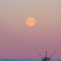 A full moon of may sets on the Gulf as a troller heads out for the morning bite