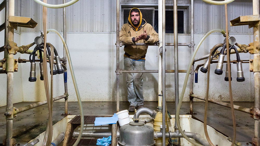 "Justin Parks checks in with neighbor helping him milk his herd Thursday, Nov. 19, 2015. Parks is the only full-time employees on the farm and gets spuratic help from family and friends. ""Help is terribly hard to find,"" he said."