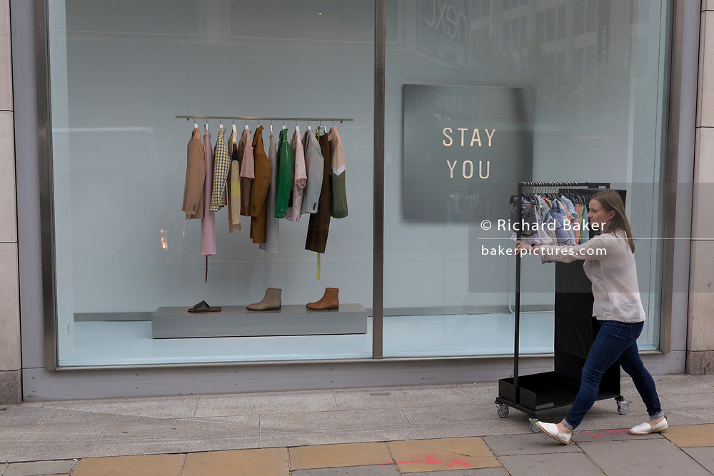 A member of staff from the retailer Zara, pushes a rack of childrens' clothes on New Bond Street, on 16th April 2018, in London, England.