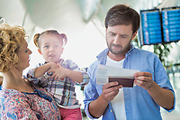 Man looking on boarding pass while his wife is carrying their daughter in airport