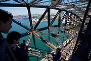 "Sydney Harbour Bridge, affectionately dubbed the ""coat hanger"", was completed in 1932. It is open to visitors by joining the famous ""BridgeClimb"" since 1998. Here shown is ""The Discovery Climb"" ascending and descending along the lower arches of the bridge, while also providing a view from the top in the middle. View over Sydney Harbour and the Opera House."