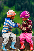 Two young children sit along the edge of the Rohtang Pass in Himachal Pradesh, India. The 13,000 foot pass, near Manali, in the Pir Panjal Range of the Himalayas connects the Kullu Valley with the Lahaul and Spiti Valleys.