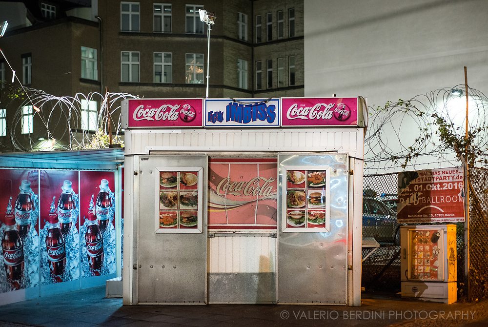 A Food stall, in front of a police station, in a Berlin night.