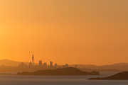 Summer is here!  A warm orange sunset over Auckland's cityscape, as viewed from Waiheke Island, New Zealand.