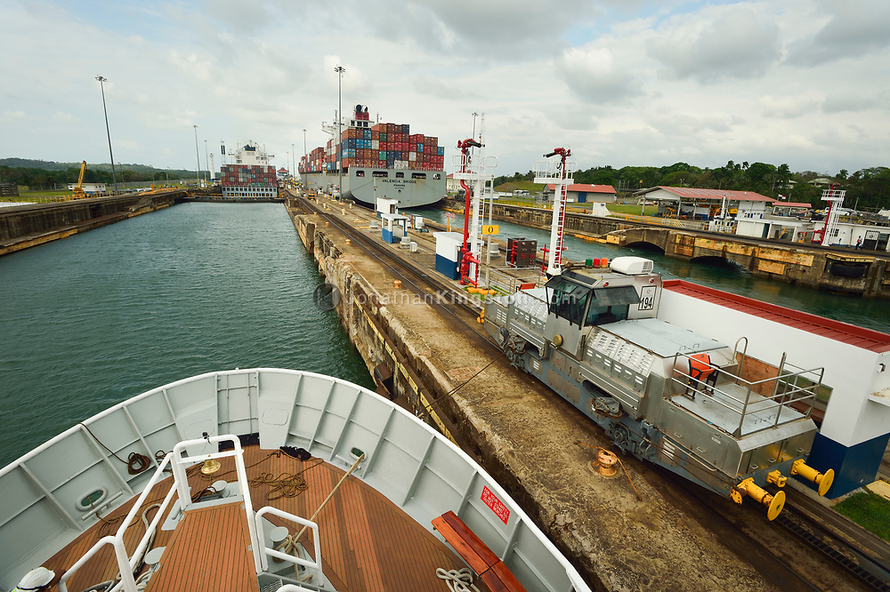View from the bow of a small passenger ship as it transits the Gatun locks, guided by a metal mule, on the Atlantic side of the Panama Canal, Panama.