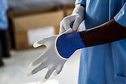 Dr Peter Githua puts on his gloves before heading to the red zone, patient ward. IOM Ebola treatment unit (ETU) in Sinje, Liberia. The ETU brings clinical care closer to Ebola patients in Grand Cape Mount County, where active transmission persists in hotspots such as Tewor, Porkpa and Gola Konneh districts. This treatment facility is one of three USAID-supported Ebola treatment units managed by IOM including others in Tubmanburg, Bomi County and Buchanan, Grand Bassa County.<br /> <br /> The new treatment facility opens with 10 beds and the capacity to rapidly scale up to 50. USAID&rsquo;s Office of U.S Foreign Disaster Assistance is supporting IOM to operate the ETU in partnership with Liberia&rsquo;s Ministry of Health and Social Welfare (MOHSW) as part of the Government of Liberia&rsquo;s Ebola response strategy.<br /> <br /> The treatment unit in Sinje is run by 23 medical professionals from Kenya, South Africa, Tanzania, Uganda and Ukraine. IOM also recruited and trained 114 Liberians from Grand Cape Mount County to offer clinical and non-clinical care within the facility. The staff received training from the World Health Organisation (WHO) and the MOHSW, including hands-on training at the IOM-managed ETU in Tubmanburg, Bomi County.UNMEER/Martine Perret. 27 January 2015