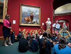 Culture Secretary Fiona Hyslop watches as National Galleries Educator Darren Robertson tells pupils from St Ninians primary school - all wearing antlers to mark the occasion - about the  launch the nationwide tour of the famous 'Monarch of the Glen' painting by Sir Edwin Landseer.<br /> <br /> &copy; Dave Johnston/ EEm