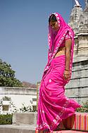 A woman wearing a bright pink sari walking down the steps at the main Jain temple at Ranakpur.