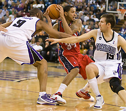 November 27, 2009; Sacramento, CA, USA;  New Jersey Nets guard Devin Harris (34) is defended by Sacramento Kings forward Kenny Thomas (9) and guard Beno Udrih (19) during the fourth quarter at the ARCO Arena. Sacramento defeated New Jersey 109-96.