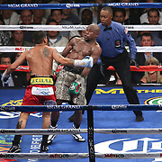 LAS VEGAS, NV - SEPTEMBER 13: Floyd Mayweather Jr. (R) leans back to avoid a punch by Marcos Maidana, as referee Kenny Bayless observes, during their WBC/WBA welterweight title fight at the MGM Grand Garden Arena on September 13, 2014 in Las Vegas, Nevada. (Photo by Alex Menendez/Getty Images) *** Local Caption *** Floyd Mayweather Jr; Marcos Maidana; Kenny Bayless
