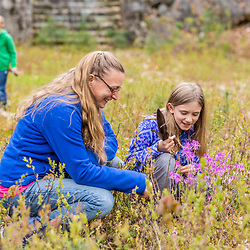 A mom and daughter check out a blooming rhodora shrub at the Stonehouse Forest in Barrington, New Hampshire.