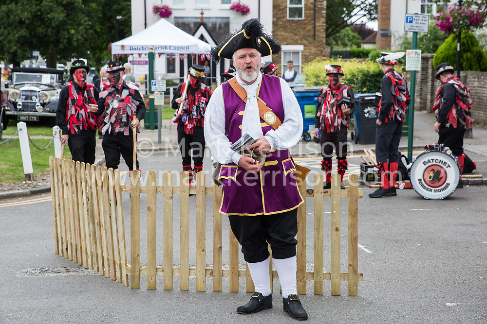 Datchet, UK. 30 June, 2019. Chris Brown, Official Town Crier of the Royal Borough of Windsor and Maidenhead, announces a performance by Datchet Border Morris, an all male Border Morris side with a mixed band who perform dances in the English border Morris style, before the arrival of pre-1905 vehicles taking part in the 48-mile Ellis Journey from Micheldever station near Winchester to Datchet.