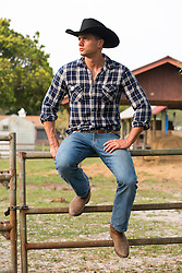 handsome cowboy sitting on a fence at a ranch
