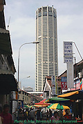 The Komtar Tower rises over a busy shopping district filled with people shopping in Penang, Malaysia.