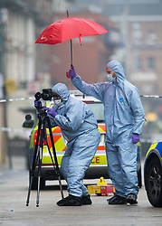 © London News Pictures. 24/08/2013. Kilburn, UK. Crime scene forensics shelter underneath an umbrella while gathering evidence at the scene of a double shooting on Kilburn High Road in North London in which two women were injured. One is  in critical condition, the condition of the second woman is currently unknown. Photo credit: Ben Cawthra/LNP