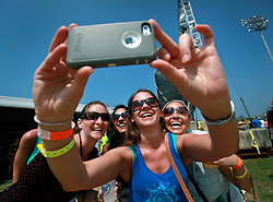 25 April 2014. New Orleans, Louisiana.<br /> The New Orleans Jazz and Heritage Festival. <br /> Kristin Huff takes a selfie with friends.<br /> Photo; Charlie Varley/varleypix.com