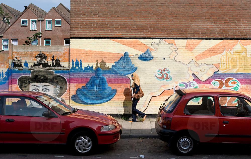 """Nederland Den Haag 31 augustus 2008 2080831 Foto: David Rozing..Moslima loopt voor indiase muurschildering in achterstandswijk Schilderswijk langs. In de wijk zijn verschillende muurschilderingen aangebracht om het multiculturele karakter van de schilderswijk weer te geven. Per muur is een beeld gecreerd uit een cultuur: Indiaas, Afrikaans, Nederlands, Surinaams, Antilliaans en Arabisch.  Doel van de muurschildering: """" Om graffiteurs en onroerend goed eigenaren op een kunstzinnige wijze met elkaar te laten samenwerken en onder afspraak dat de graffiteur ophoudt met illigaal taggen. De graffiteur wordt betaald en krijgt de opdracht om deze muurschilderingen aan te brengen. Meer info: Yolande Weerdenburg 06 24613835.De schilderwijk is een van de 40 wijken van Vogelaar. Deze lijst van 40 Nederlandse probleemwijken is op 22 maart 2007 door Minister Ella Vogelaar van Wonen, Wijken en Integratie bekend gemaakt. De minister duidde deze wijken aan met prachtwijken. In deze wijken zullen gedurende de kabinetsperiode Balkenende IV extra investeringen worden gedaan gezien stapeling van sociale, fysieke en economische problemen die zich daar voordoen..De wijk is in de tweede helft van de 19e eeuw gebouwd. Het is een van de armste wijken in Nederland. Zo'n 87% van de 33.123 geregistreerde bewoners is van niet-Westerse afkomst -- met name Turks, Surinaams en Marokkaans..De Schilderswijk is rijk aan verschillende culturen die boven en naast elkaar leven. Er is veel keuze in voedselaanbod in cafés, kleine restaurants, bars en supermarkten. Er is de Haagsche markt en er zijn winkels waarin verschillende culturen hun deur openen om iets nieuws te verkopen, zoals sieraden- en kledingwinkels. Allerlei stedelijke activiteiten liggen op loopafstand van de Schilderswijk. De Haagse binnenstad ligt 5 minuten lopen vanaf de rand van de Schilderswijk. Tram en ander openbaar vervoer zijn te bereiken op 5 tot 10 minuten loopafstand...Foto David Rozing"""
