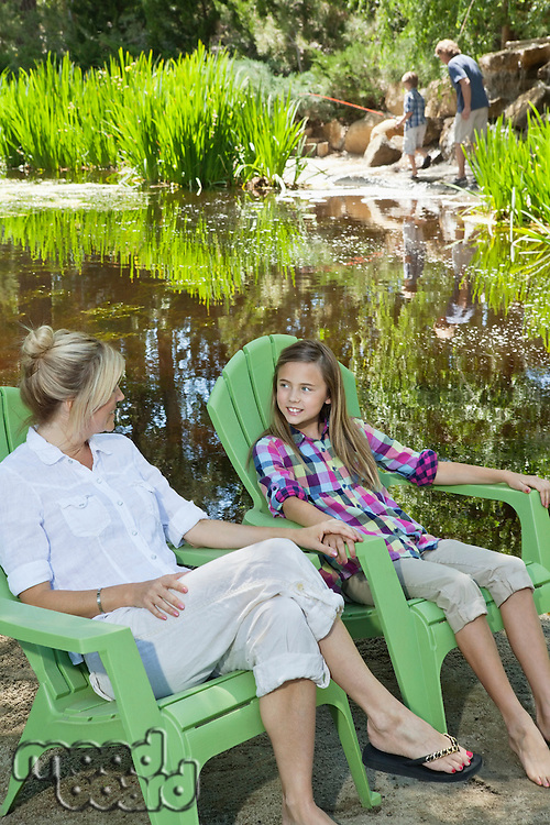 Mother and daughter relaxing on chairs with man and boy fishing in the background