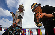 """Two contestants of the world worm charming competition bend down to use a fork and a recorder to encourage invertebrates out of the ground in a field at Willaston, Cheshire, England. One woman wears a plastic helmet and the other has a worm illustrated t-shirt with a handmade sign that reads""""Ive got the worms!"""" There are 18 rules translated into 30 languages (including Tibetan) but here these two daft ladies use music and garden tools to vibrate the earth helping the worms to the surface in a 3-metre square plot. International flags are behind but local hero Tom Shufflebotham's 1980 world record still stands at 511 worms out of the ground in half an hour. The fattest  worm ever caught weighed 6.6 grams, the most succesful method being hand vibrating a four tyne garden fork inserted approximately 15cms into the turf, known as 'twanging'."""