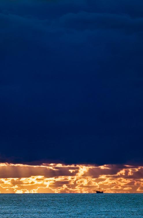 Heavy blue dawn & golden horizon with fishing boat shot off Florida coast USA