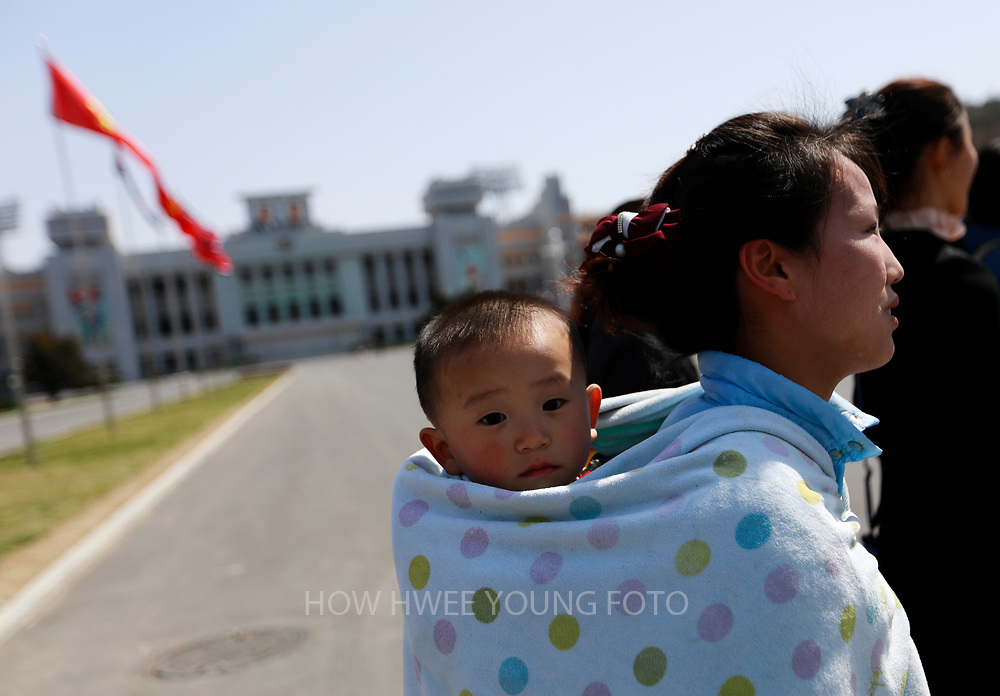 A North Korean woman carrying her son on her back outside the Kim Il Sung Stadium in Pyongyang, North Korea, 12 April 2017. North Koreans prepare to celebrate the 'Day of the Sun Festival', 105th birthday anniversary of former North Korean supreme leader Kim Il-sung in Pyongyang on 15 April.