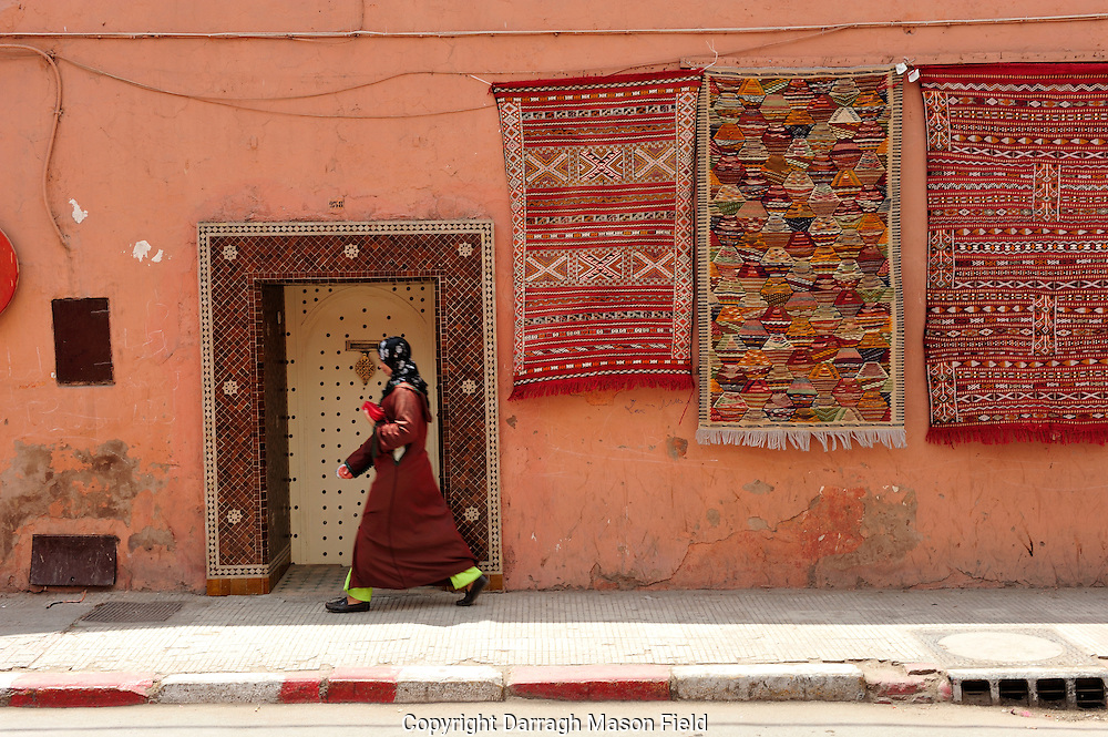 Woman walking by a tiled doorway and carpets hanging in the wall in Marrakesh
