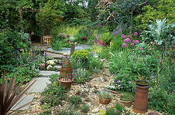 View showing planted gravel area, wooden path around pond, pergola and woodland area in background. Cardoon, alliums, iris and primulas.