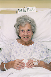 Portrait of elderly woman sitting up in hospital bed on ENT Ward waiting to be seen by nurse,