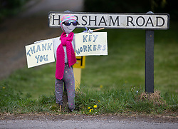 © Licensed to London News Pictures. 27/04/2020. Capel, UK. A scarecrow tribute to key workers has been placed on the side of the road in the Surrey village of Capel. Residents of the village have resurrected their summer tradition of scarecrows in tribute to NHS medical staff and other key workers. Up to 30 of the life size home made doll like characters can be seen in front gardens throughout the village. The public have been told they can only leave their homes when absolutely essential, in an attempt to fight the spread of coronavirus COVID-19 disease. Photo credit: Peter Macdiarmid/LNP