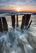 Lake Michigan waves rushing into shore as the sun nears the horizon.