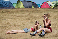 © Licensed to London News Pictures . 19/07/2013 . Suffolk , UK . Two women sunbathe in the heat in front of tents at The Latitude music and culture festival in Henham Park , Southwold . Photo credit : Joel Goodman/LNP