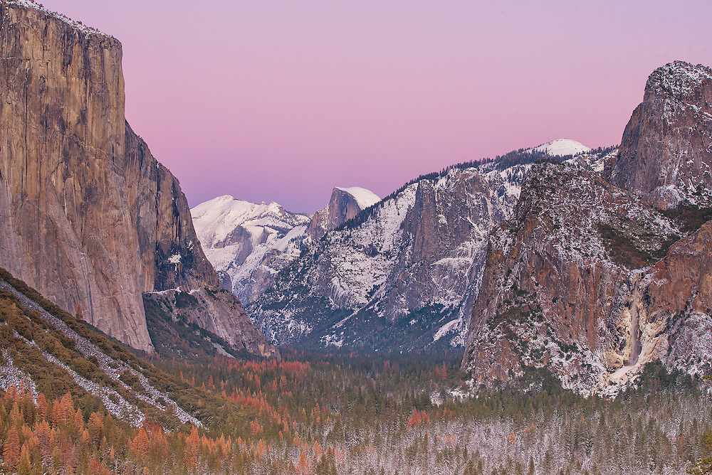 Serene sunset as seen from the Tunnel View Outlook at Yosemite National Park, California. It took an incredible 65 million years for a flowing glacier to carve and polish massive plutonic rocks along its way to form this valley. Plutonic rocks, are formed because of molten rocks cooling at a very slow pace, underground and were exposed only after erosion caused by the moving glacier.