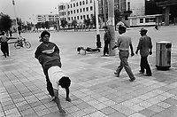 Xinjiiang Uygur Autonomous region. Kashgar. Wrestlers exercise a street scene in one of the main streets of Kashgar.