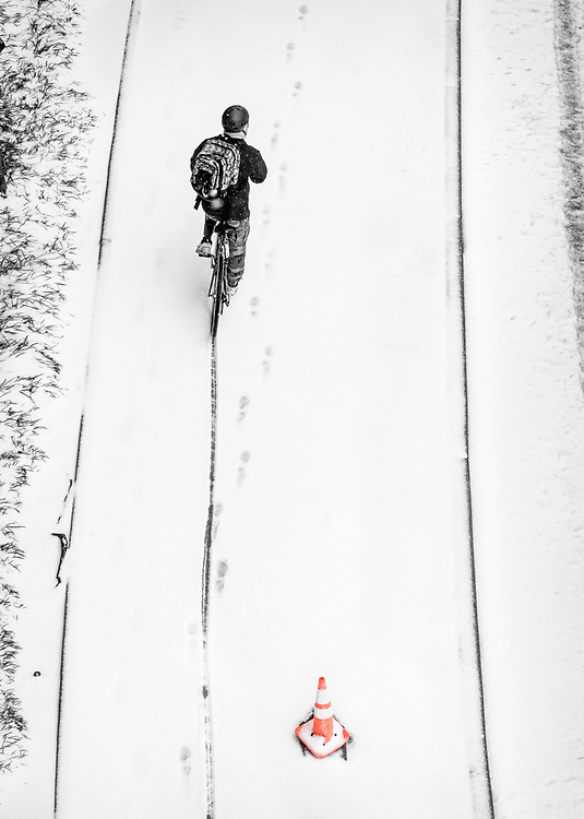 Interesting textures and patterns as this cyclist makes their way through the snow and slush in downtown Greensboro.