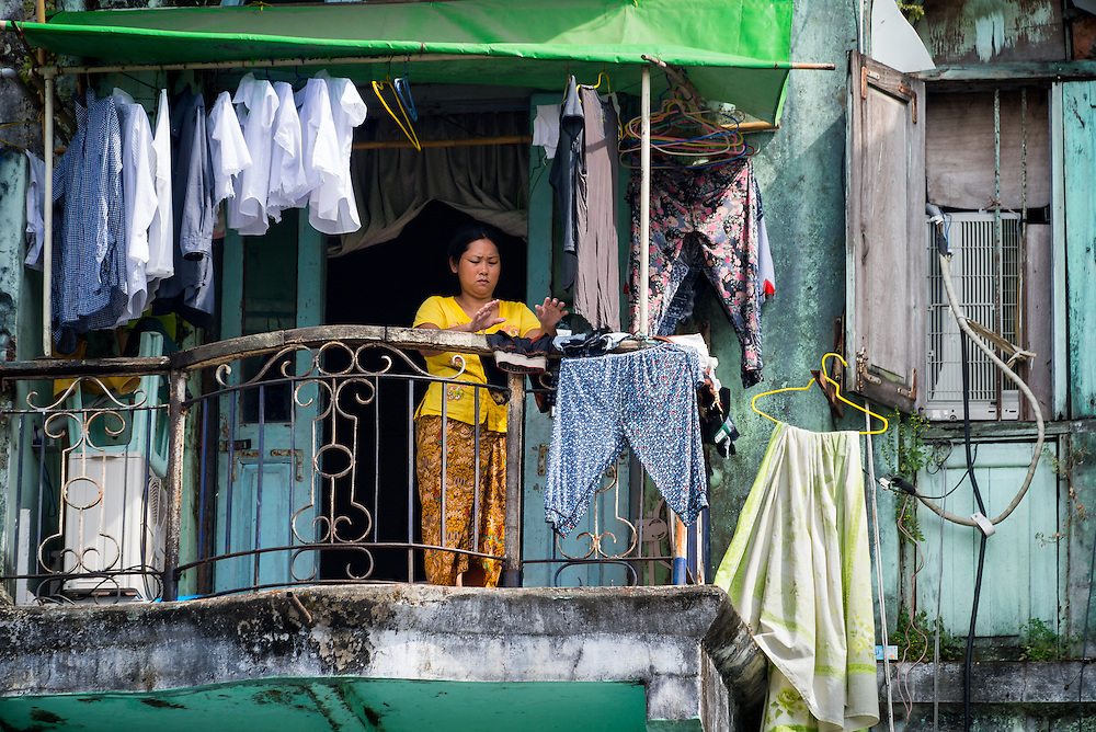 YANGON, MYANMAR - CIRCA DECEMBER 2013: Portrait of Burmese woman hanging clothes in a balcony in Yangon.