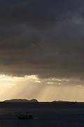 The sun rises over Halfmoon Bay, silhouetting Herekopare Island and Bunker Islets, Oban, Stewart Island, New Zealand