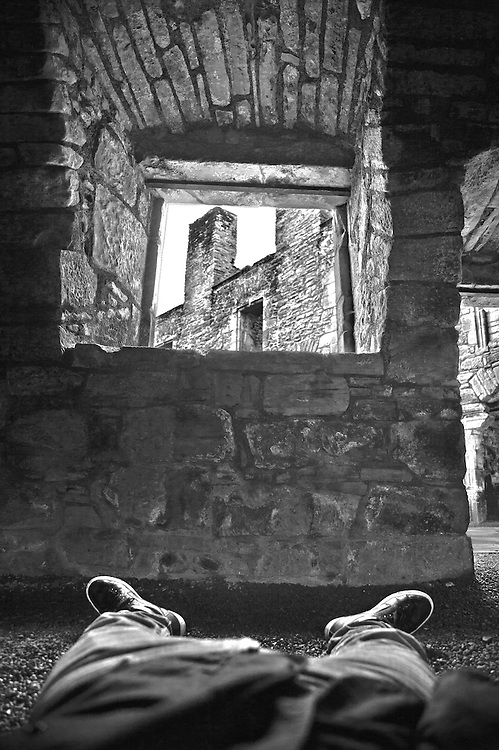 Picture shows a man lying down on the floor of Caerlaverock Castle with a view loking through a stone window showing the castle walls in the background. Possible use includes advertising, magazine, editorial, promotion, book publishing, creative, etc.