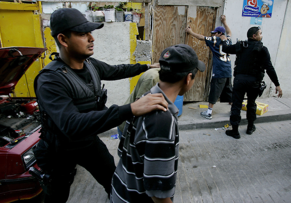Tijuana Police agents search residents for illegal contraband during a drug sweep in Colonia Chula Vista in Tijuana, Mexico